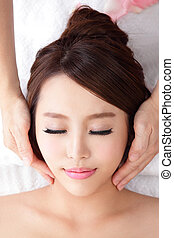 woman enjoy receiving face massage at spa