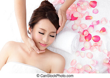 woman enjoy receiving face massage at spa with roses