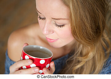 Beautiful young woman enjoying cup of tea at home
