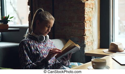 Beautiful young woman enjoying funny book in cafe reading...