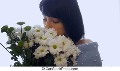 Beautiful, young woman enjoys a bouquet of flowers. White Camomiles. Love, offer of the hand and heart.