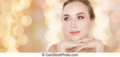 beautiful young woman face and hands over lights - beauty,...