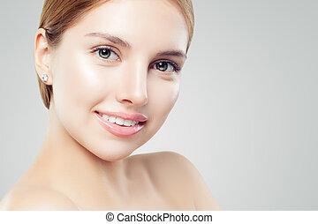 Beautiful young woman face, closeup portrait. Girl smiling