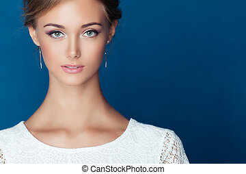 Beautiful young woman face on blue background, closeup portrait
