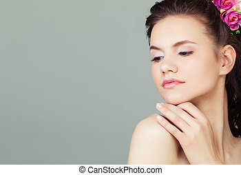 Beautiful young woman face on grey background, closeup portrait