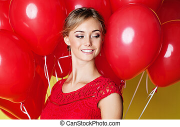 Beautiful young woman face on yellow background with balloons, closeup portrait