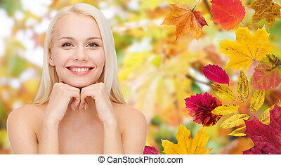 beautiful young woman face over autumn leaves
