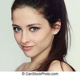 Beautiful young woman face with natural makeup looking...