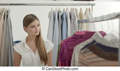 Beautiful girl shopping for clothes and shirt in fashion store