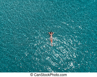 Beautiful young woman floating in crystal clear water, aerial shot