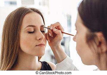 Beautiful young woman gets eyebrow correction procedure.