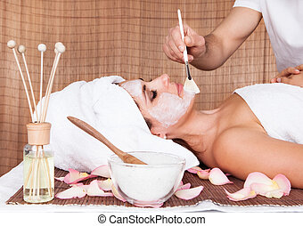 Beautiful young woman getting facial mask