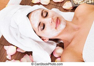 Beautiful young woman getting facial mask at spa studio