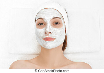 woman getting facial mask in spa