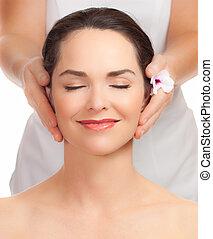 Beautiful young woman getting facial massage