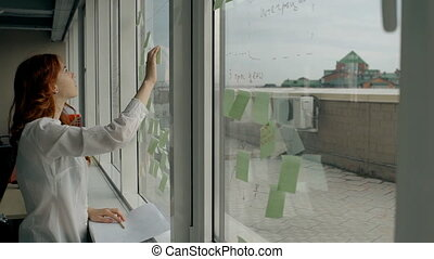 Beautiful young woman glues stickers on window standing in...