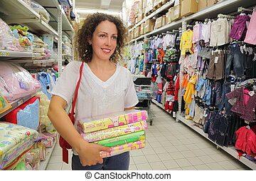 beautiful young woman goes in big store, childish clothing, bedding