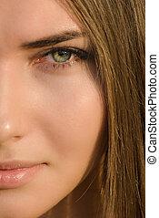 Beautiful young woman half face closeup