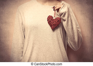beautiful young woman hand holding heart shaped toy on the wonderful grey background