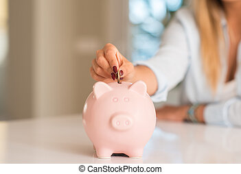 Beautiful young woman hands holding a coin investing in to a piggy bank at home. Business concept.