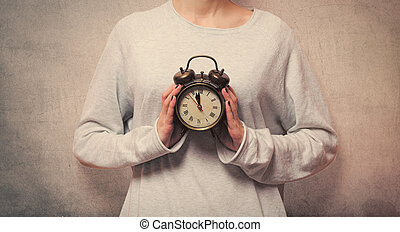 beautiful young woman hands holding a vintage alarm clock on the wonderful grey background