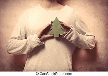 beautiful young woman hands holding fur tree shaped toy on the wonderful grey background