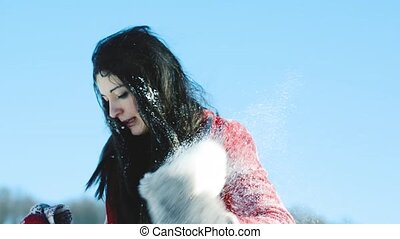 Beautiful young woman having fun in the snow. Sunny white...