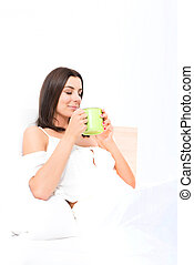 Beautiful young woman having her first coffee in bed