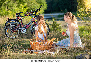 Beautiful young woman having picnic with girl at river