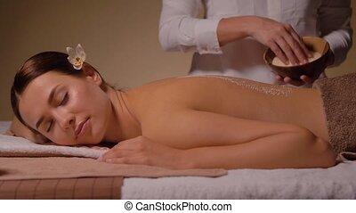 beautiful young woman having salt massage at spa - wellness,...