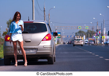 Beautiful young woman having troubles with her car