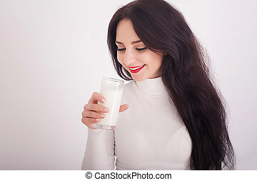 beautiful young woman holding a glass of milk