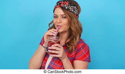 Beautiful young woman holding a red smoothie