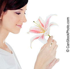Beautiful young woman holding a white lily at face isolated over