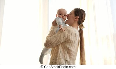 Beautiful young woman holding and lifting up her cute little baby. Concept of family happiness and parenting