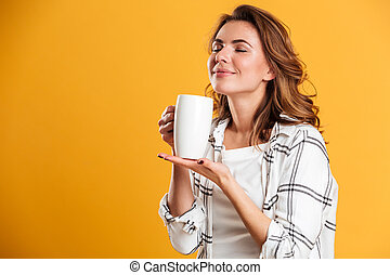 Beautiful young woman holding cup of tea. Eyes closed.