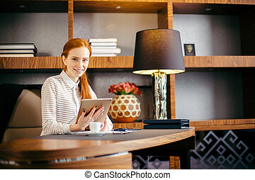 Beautiful young woman holding digital tablet and looking at camera with smile