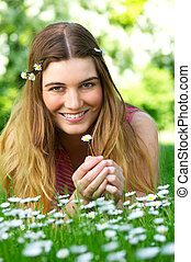 Beautiful young woman holding flower in the park
