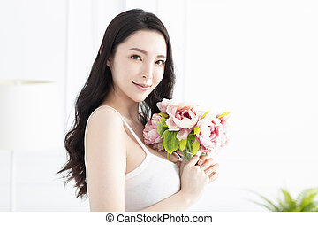 beautiful young woman holding flower
