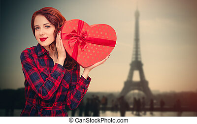 beautiful young woman holding gift on the wonderful eiffel tower background