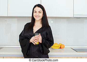 Beautiful young woman holding glass of orange juice