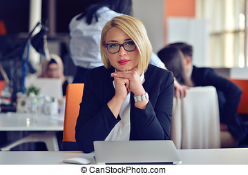 Beautiful young woman holding hands on chin and smiling while sitting at her working place