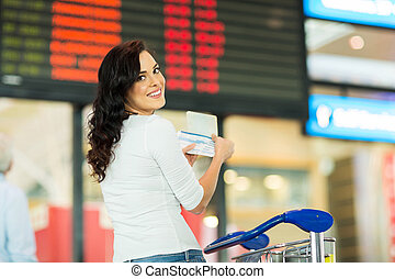 young woman holding passport and boarding pass in front of fligh