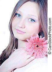 Beautiful young woman holding pink flower