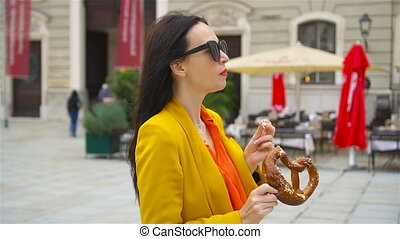 Beautiful young woman holding pretzel and relaxing in park -...