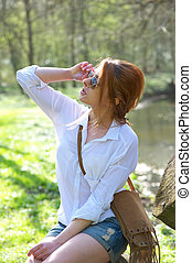 Beautiful young woman holding sunglasses outdoors