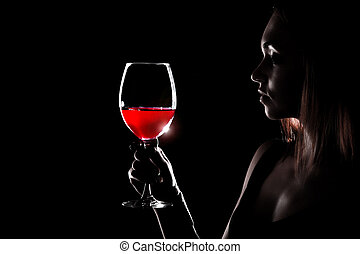 Beautiful young woman holding the glass of a red wine