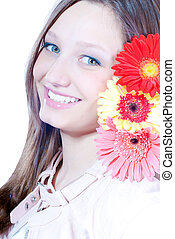 Beautiful young woman holding three flowers