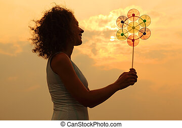 beautiful young woman holding toy whirligig and smiling at sunset