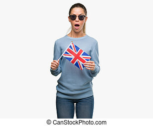 Beautiful young woman holding UK flag scared in shock with a surprise face, afraid and excited with fear expression